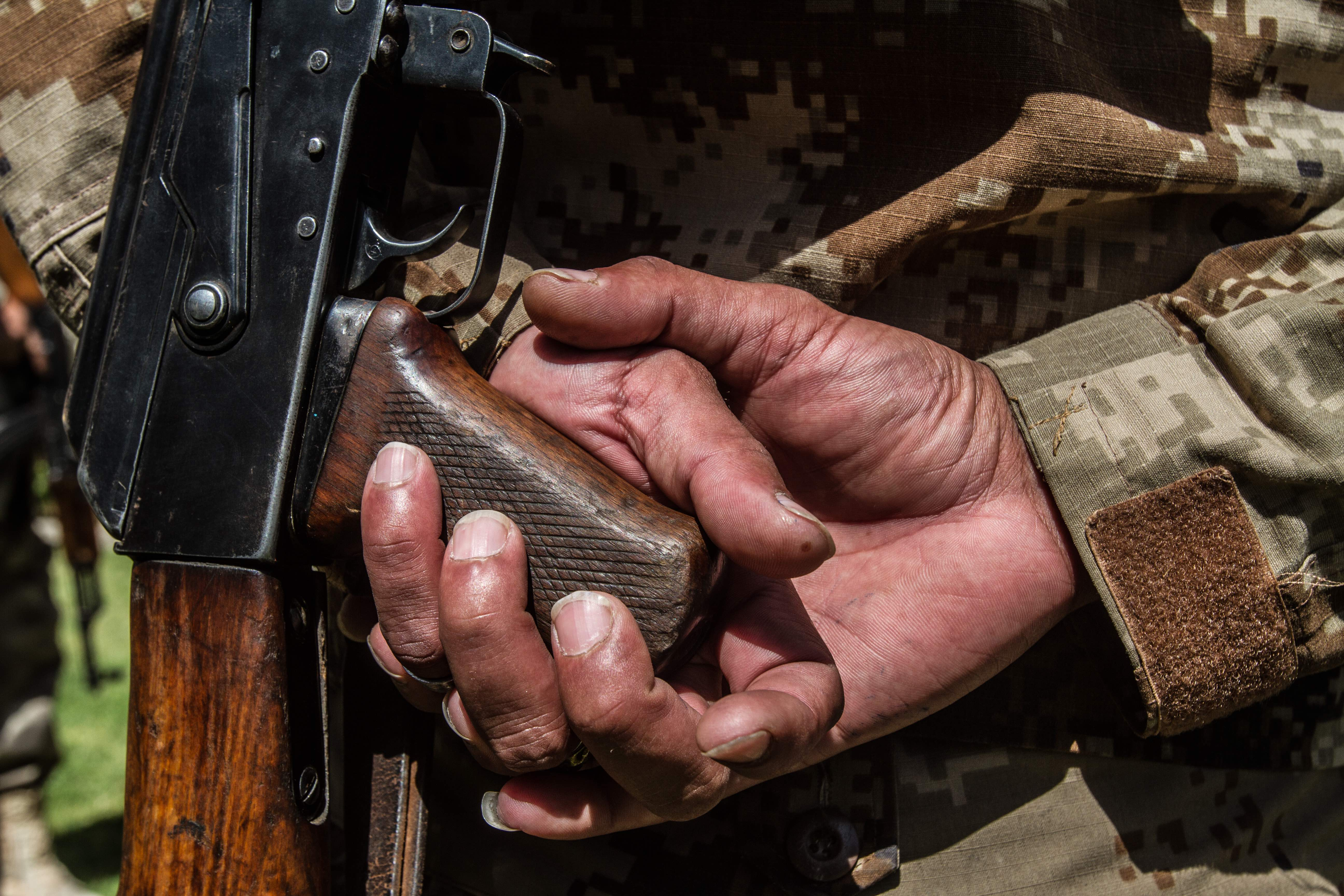 An officer from the militia holds his live weapon. © Jan Husar