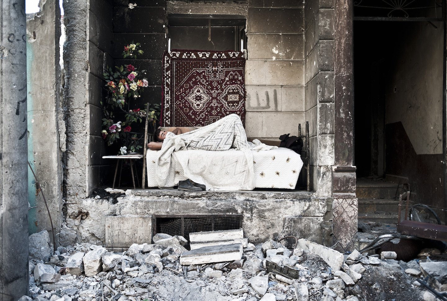Decorating the outpost, An FSA fighter from Nour De Zenky makes a space into a small home in the neighbourhood of Hanano. Hanano once had 400,000 civilians living in the area, now there are less than 4000. Aleppo 2014. © Jacob Simkin.