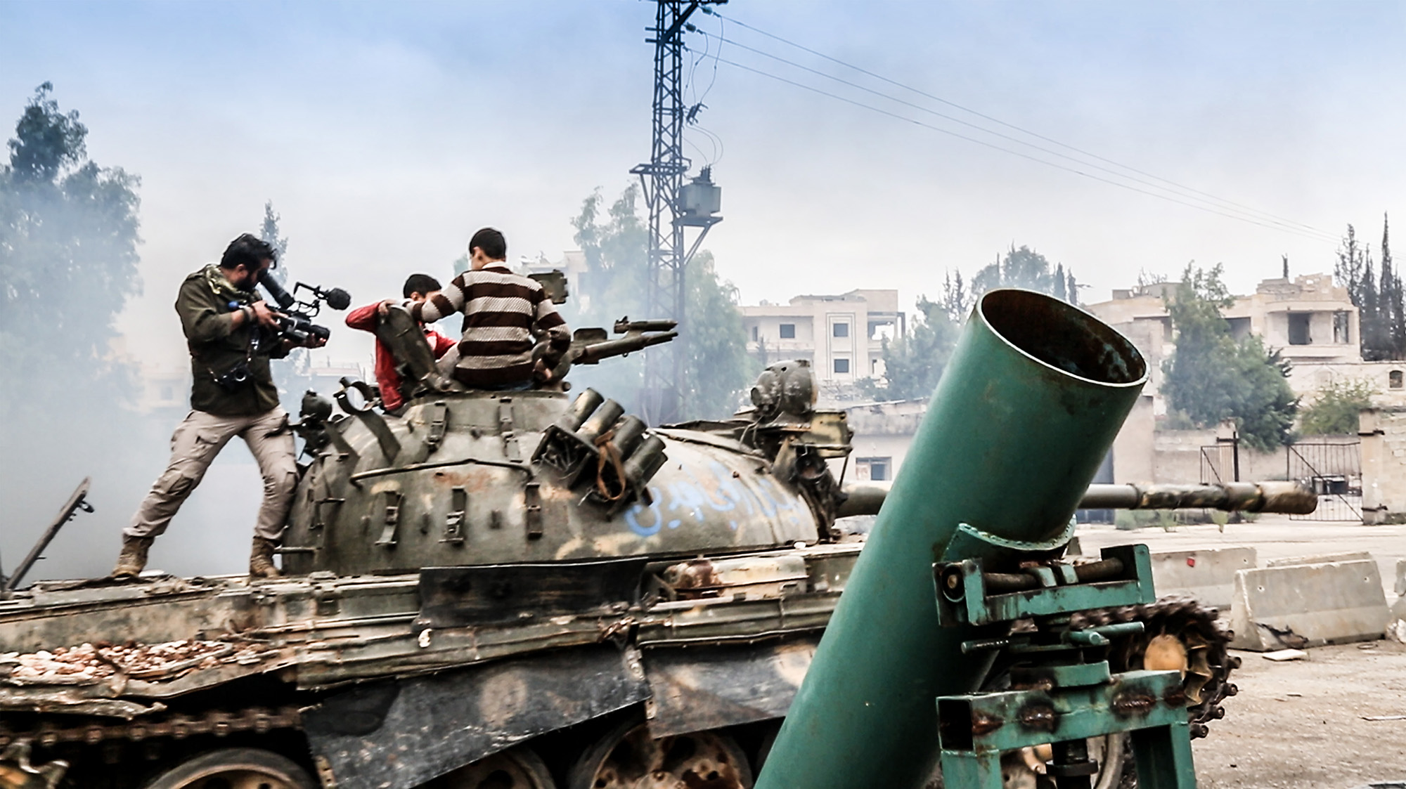 Riding around on a newly acquired SAA tank captured by Jasysh as Mujahdeen films for Vocativ in Syria 2014. © Jacob Simkin.