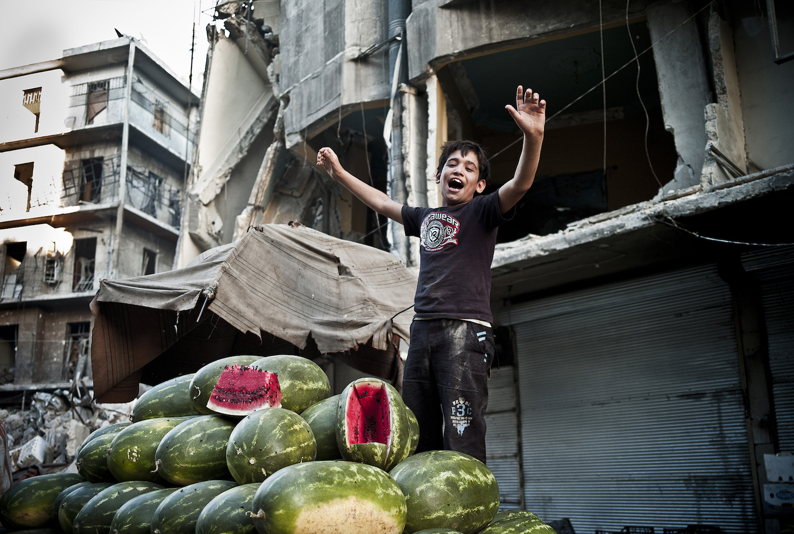 Ahmed sells watermelons during the month of Ramadan in Shaar district of Aleppo. Aleppo's markets are under constant threat of barrel bomb attacks by the regime. I returned back in 2015 to Syria during Ramandan, and the marketplace had been heavily bombarded and Ahmed had been wounded and killed. Aleppo, 2014. © Jacob Simkin