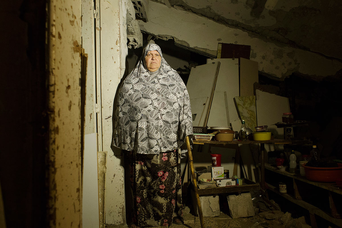 Soad Abd Rabo Al-Zaza, 65, despite her paralyzed leg, poses at her destroyed house due to Israeli air strike during the summer's 50 day's war between Israel and Hamas, as she still lives in (with her husband and other family members). Despite the fact the house is in a very dangerous condition -- it further becomes 40 cm down recently, there is no place to move, and virtually nobody has come to help yet. Alshjaia, Gaza City, Oct/ 06/ 2014.