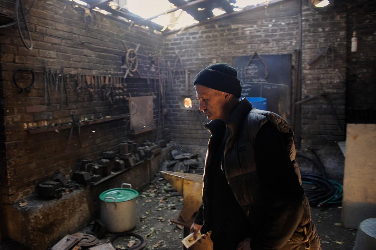 10.10.2014. Igor Lochadgin standing inside his destroyed blacksmith workshop in Pisky.