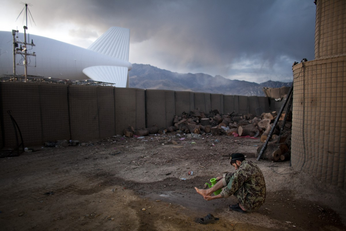 Afghanistan, Wardak, November 4, 2012 An Afghan soldier takes ablution before evening prayer near the surveillance blimp at Combat Outpost Dash-e Towp, in central Wardak Province. The blimp is on the ground at the American side of the base. Photo: Joël van Houdt for The New York Times