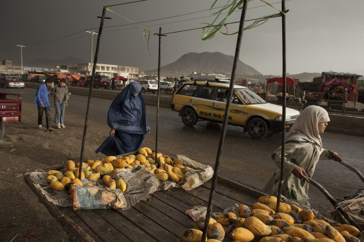 Afghanistan, Kabul, June 24, 2010 A burqa-clad woman walks past a push cart selling mangos on a Thursday during a summer rain. Photo: Joel van Houdt